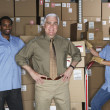 Businessman with warehouse workers in warehouse — Stock Photo