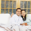 Couple sitting on the couch under a blanket together — Stock Photo #23243096