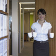 Hispanic businesswoman holding mugs — Stock Photo