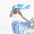 Young African woman with clothes blowing in the wind - Stock Photo