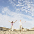 Couple standing on beach with arms outstretched — Stock Photo #23243168