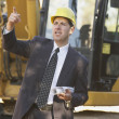 Hispanic businessman wearing a hardhat standing in front of a bulldozer — Стоковая фотография
