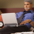 Stock Photo: Businessmusing laptop in his hotel room