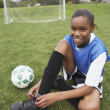 Young girl tying her soccer cleats — Stock Photo #23243306