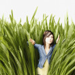 Young woman pushing back tall grass - Stock Photo