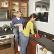 Young Hispanic couple washing dishes — Stock Photo