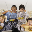 Group of children eating and watching television — Stock Photo #23243424