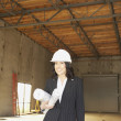 Businesswoman standing in empty warehouse with blueprints  — Stock Photo