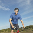 Middle-aged man riding a bicycle on a rural road — Stock Photo