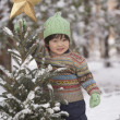 Young Asian girl with Christmas tree in snow outdoors — Stock Photo