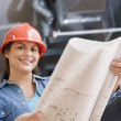 Hispanic female construction worker looking at blue prints — Stockfoto