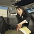 Businesswoman getting files out of the backseat — Stock Photo