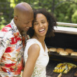 Stock Photo: Couple laughing as they barbecue together