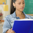 Stock Photo: Female Dominicteenager reading textbook in classroom