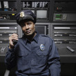 Stock Photo: Security guard sitting at control station