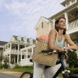 Woman riding a bike down suburban street — Stock Photo