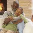 Senior Africcouple hugging on sofa — Stok Fotoğraf #23244060
