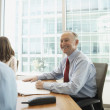 Senior businessman smiling at meeting — Stock Photo #23244076