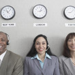 Three businesspeople under world time zone clocks — Stock Photo