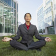 Hispanic businesswoman meditating in the grass in front of office buildings  — Stock Photo