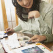 Stock Photo: Young Asian woman looking at scrapbook