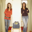 Two women standing in two fitting room doorways — Stock Photo