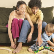 Couple and young son playing with trains — Stock Photo