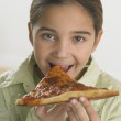 Young girl eating pizza — Stock Photo