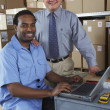 Businessman and co-worker in shipping department — Stock Photo