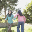 Two young Asian sisters playing outdoors  — Stock Photo