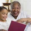 Senior woman reading to her granddaughter — Foto de Stock