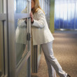 Businesswoman leaning into office — Stock Photo