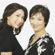 Studio shot of Asian mother and adult daughter smiling — Stock Photo #23244338
