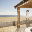 Couple in bathrobes kissing at beach — Stock Photo