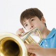 Low angle view of a young boy playing the trumpet — Stock Photo