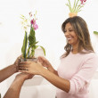 Woman taking potted flowers from male colleague — Stock Photo
