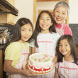 Three young Asian sisters and their grandmother holding a cake in the kitchen — Stock Photo