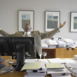 Stock Photo: African businessman at desk stretching