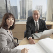 Senior Asian businessman and businesswoman looking at blueprints  — Stockfoto