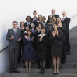 Group of businesspeople standing on outdoor stairs clapping — Stock Photo