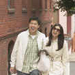 Young Asian couple walking down the sidewalk with shopping bags — Stockfoto