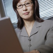 Businesswoman working at her desk — Stockfoto