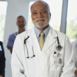 Middle-aged male African doctor with co-workers in the background — Stock Photo