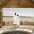 Couple in bathrobes outdoors at beach resort — Stock Photo #23244962