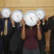 Group of businesspeople holding clocks over their faces — Stock Photo