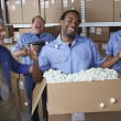 Businessman with male warehouse workers joking around - Stock Photo