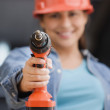 Hispanic female construction worker pointing a drill  — Stock Photo