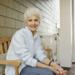 Senior woman smiling on the porch — Stock Photo