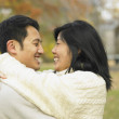 Young Asian couple hugging in the park  — Stock Photo
