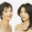 Studio shot of Asian mother and adult daughter smiling - Stock Photo